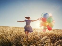 Girl running on field with balloons at sunset. Happy woman retro